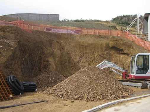 A digger and pile of dirt at an earthworks building site.
