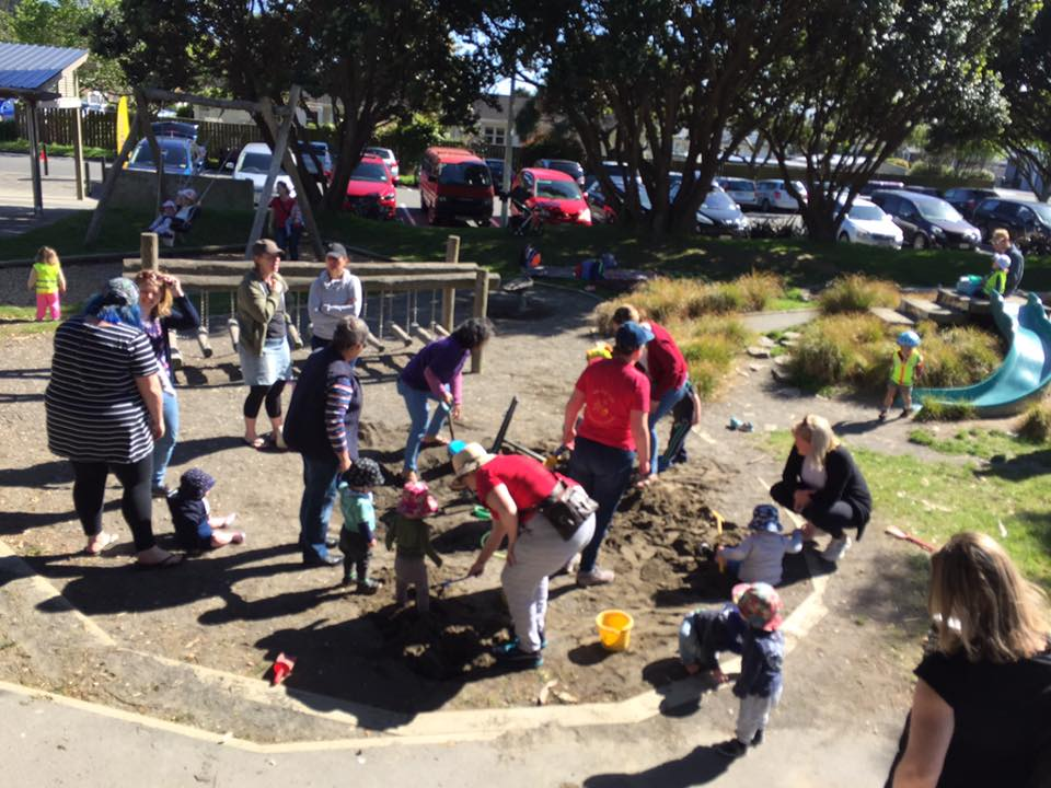 parents and kids all around a sandpit digging