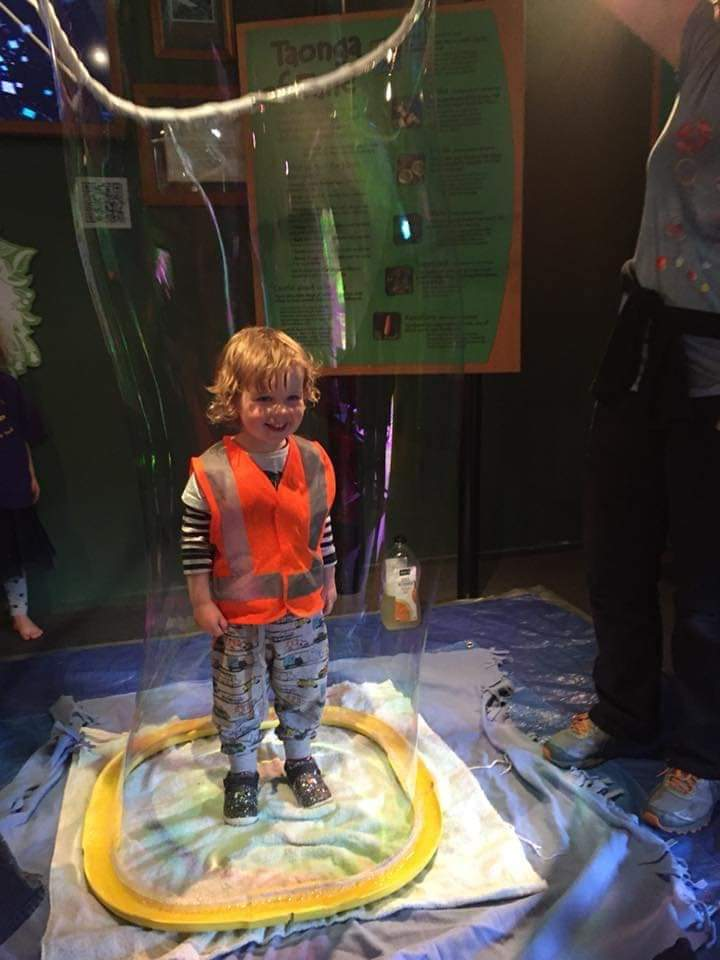 kid standing inside giant vertical bubble with huge grin on face