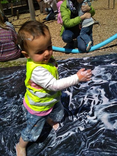 toddler dancing on a slip-and-slide covered in foam