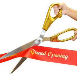 "giant gold scissors cutting a red ribbon with ""grand opening"" on it"
