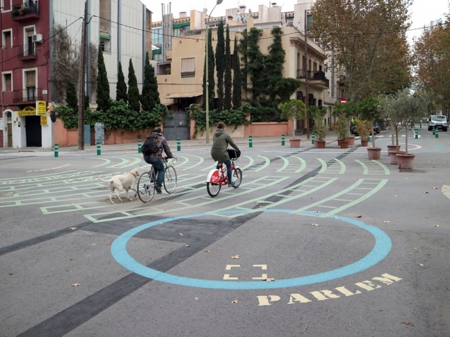 People riding through car free streets with a dog in tow