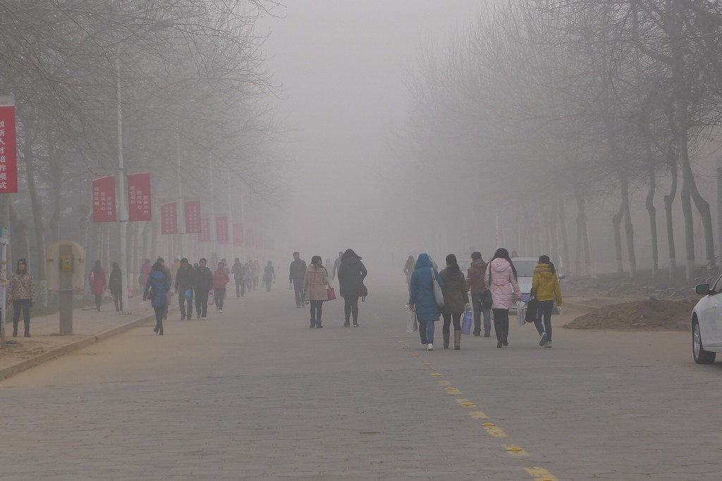 Thick smog with pedestrians walking down the street